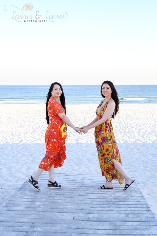 Aunt and Adult Niece holding hands on the boardwalk at Johnsons Beach in Perdido Key