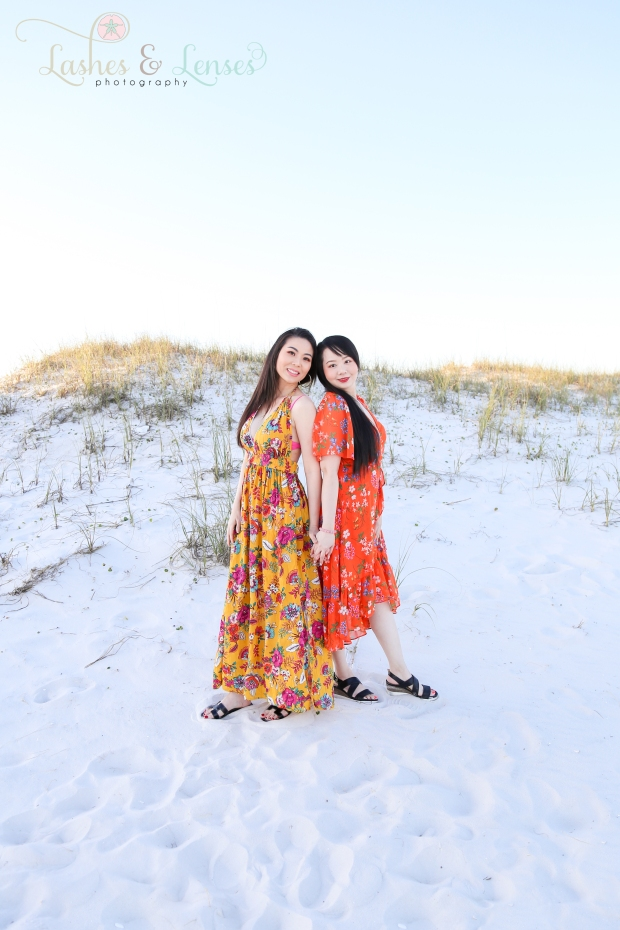Aunt and Adult Niece back to back by the sand dunes at Johnsons Beach in Perdido Key
