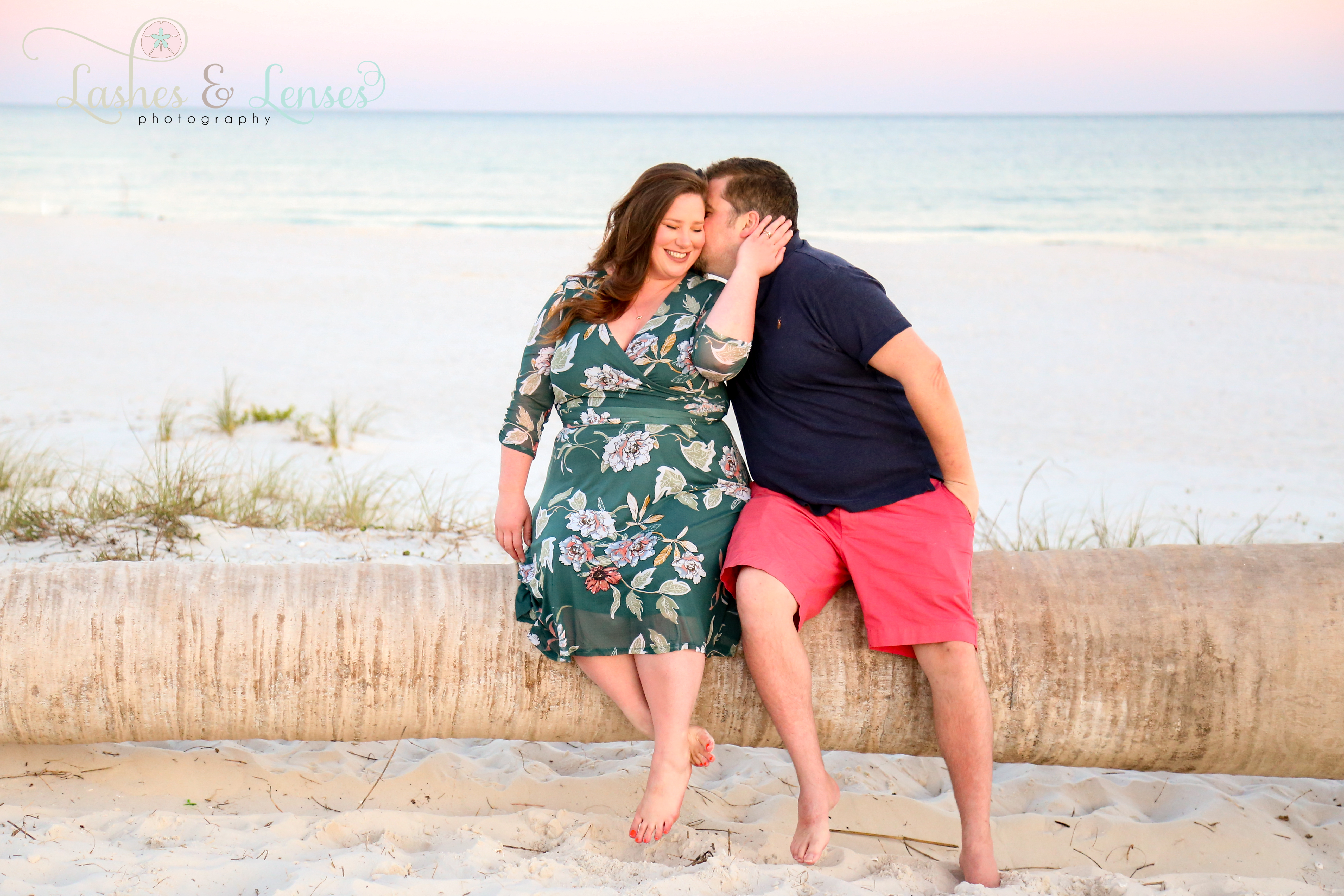 Husband kissing wife on cheek while sitting on washed up palm tree on the beach at Johnsons Beach in Perdido Key