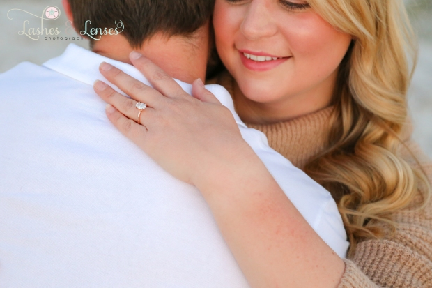 Newly Engaged Couple hugging and showing off ring at Johnsons Beach in Perdido Key