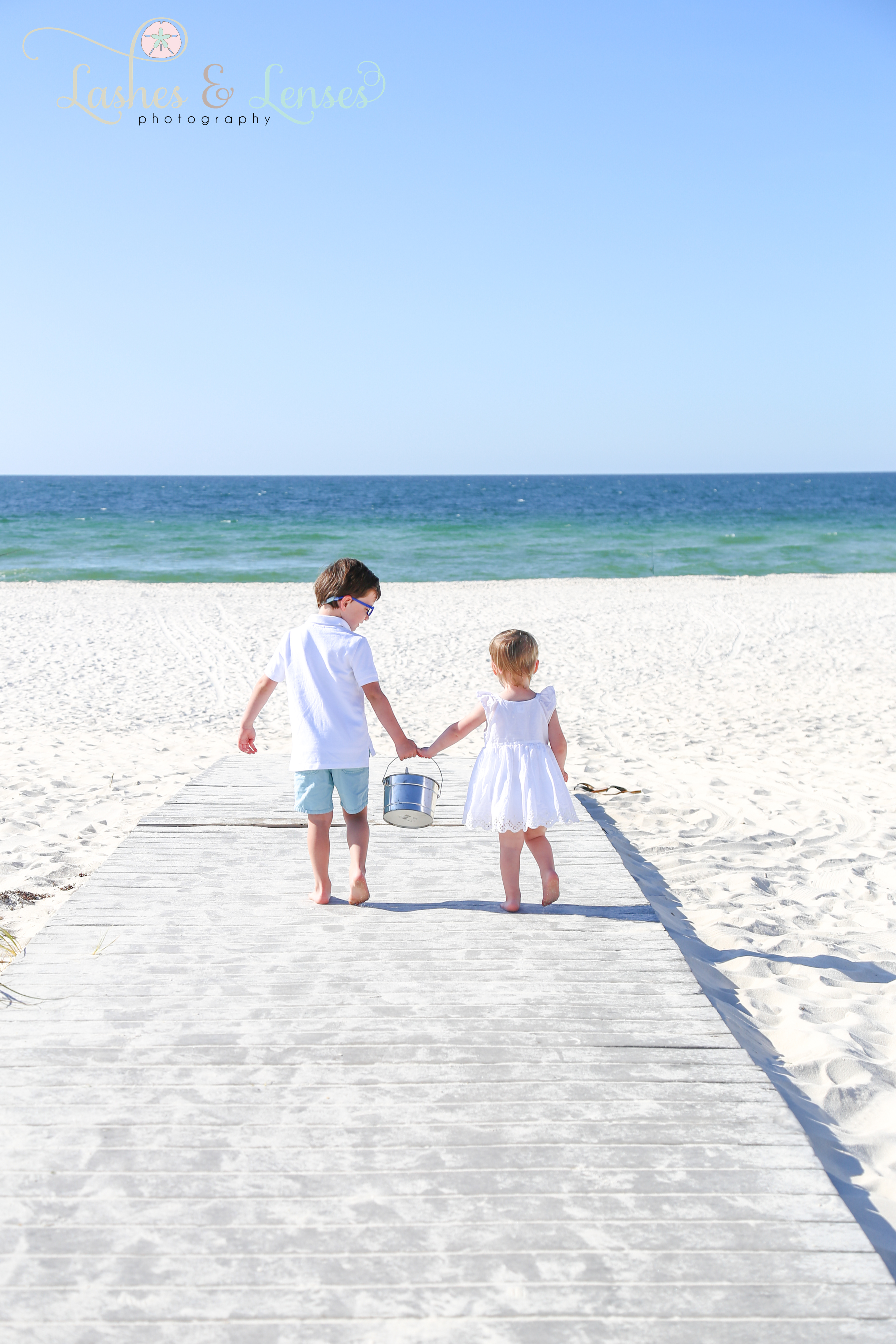 Toddler brother and sister holing hands and walking down the boardwalk at Johnsons Beach in Perdido Key