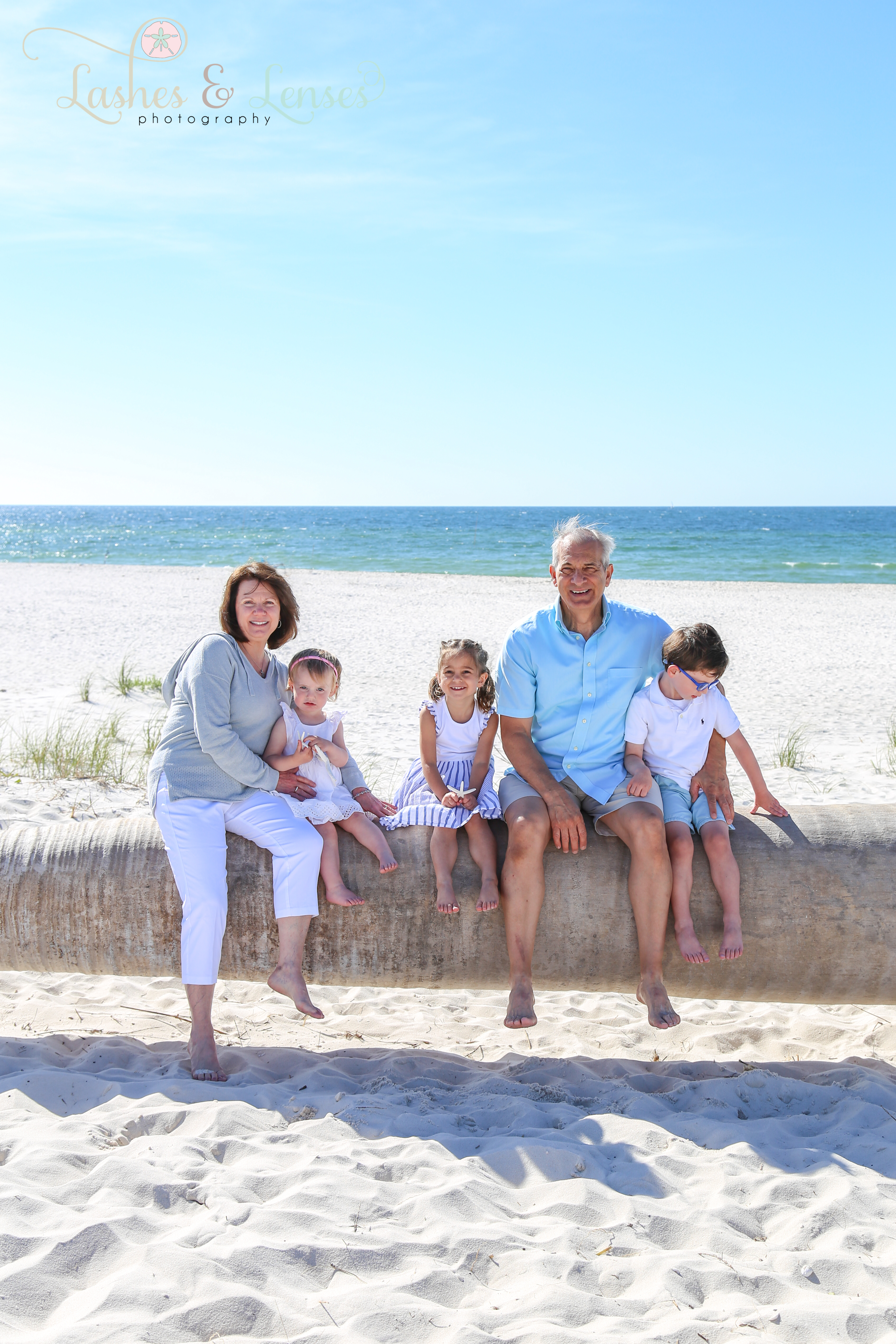 Grandparents sitting on washed up palm tree on the beach with their three small grandchildren at Johnsons Beach in Perdido Key