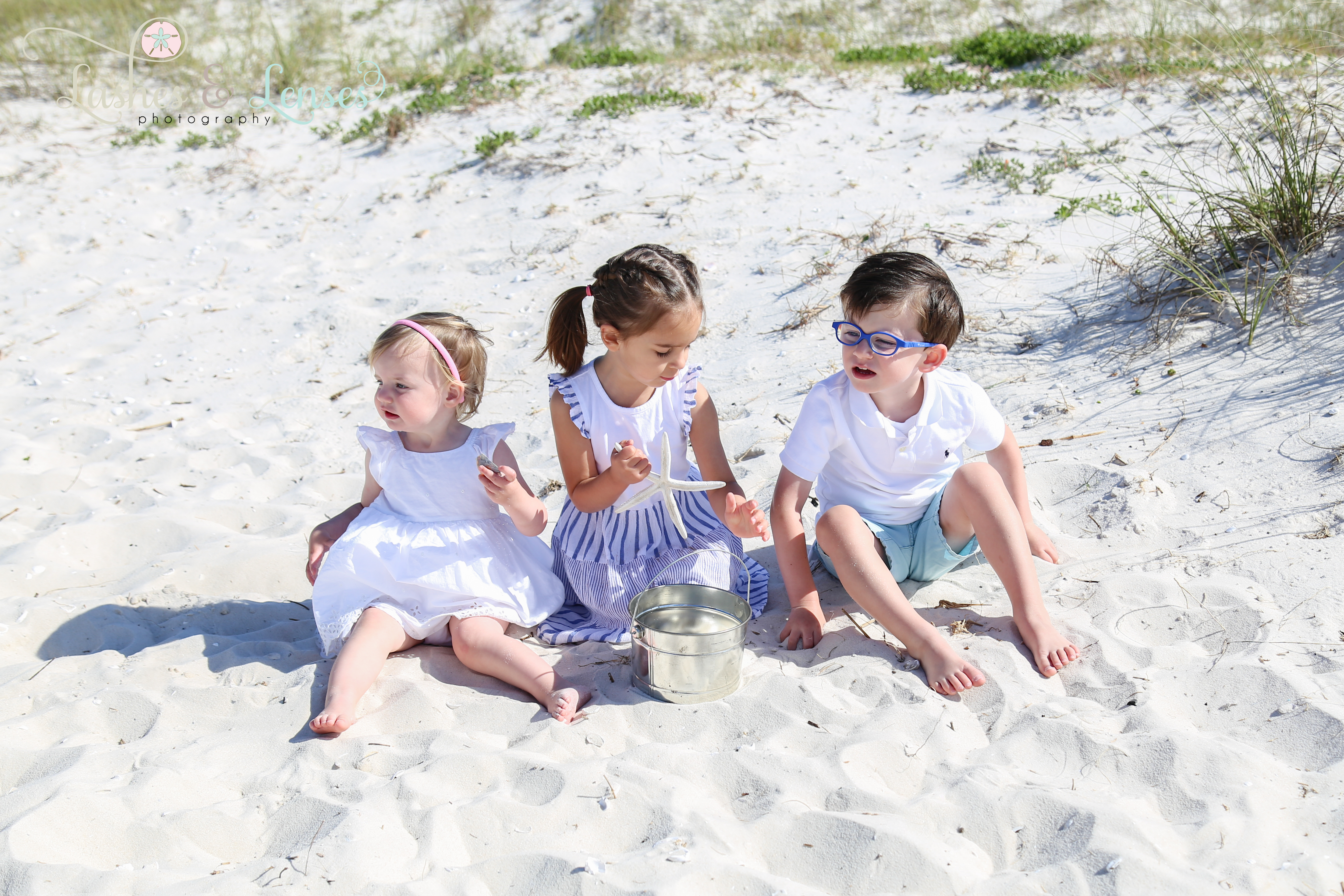 Three young cousins playing in the sand next to the sand dunes at Johnsons Beach in Perdido Key