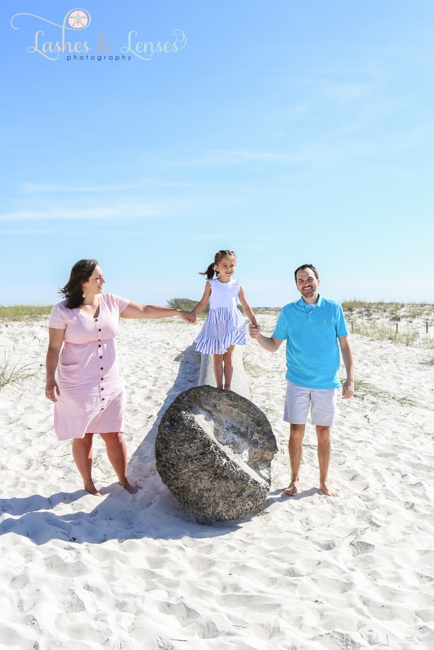 Mom and Dad with daughter on walking on top of a washed up palm tree at Johnsons Beach in Perdido Key