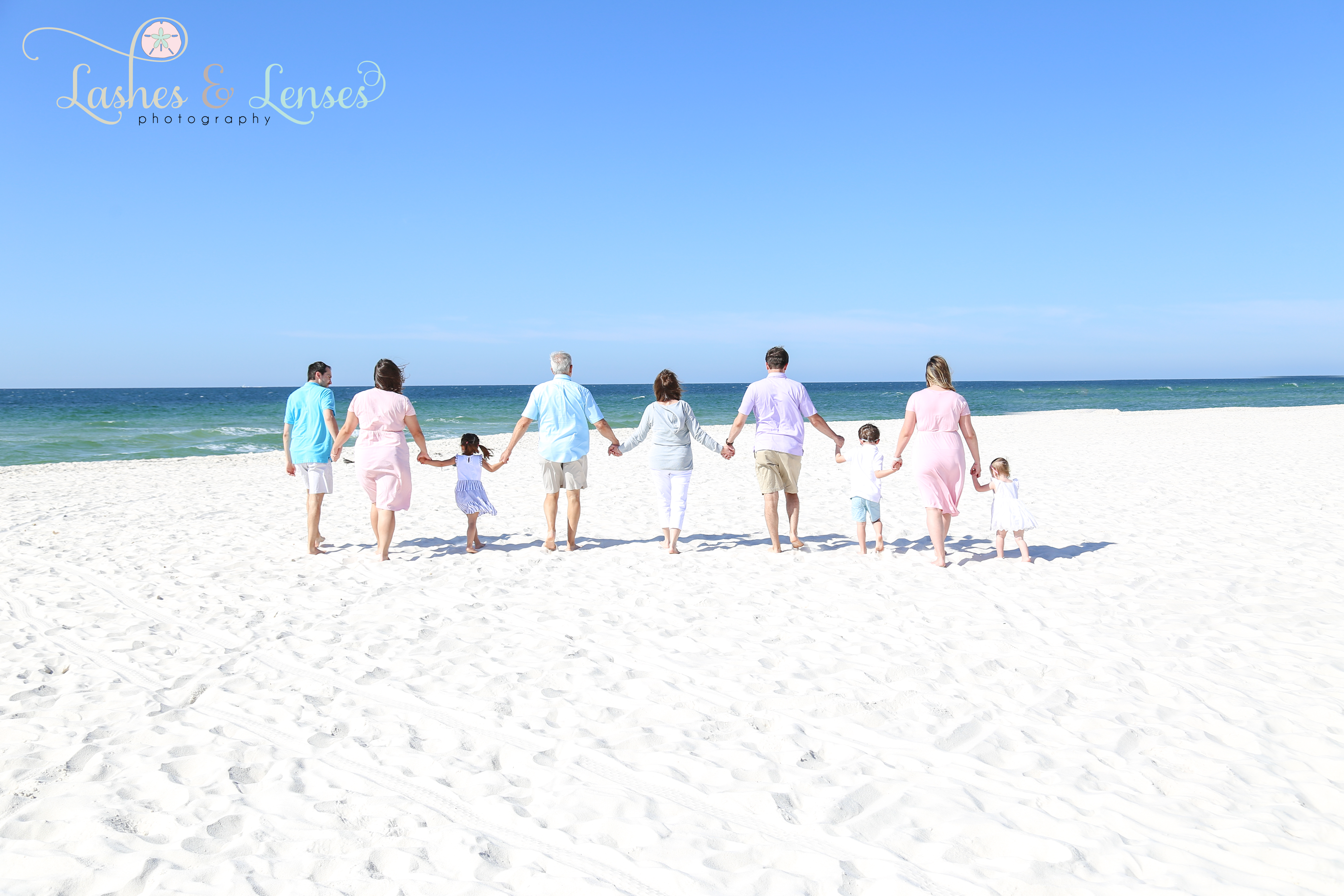 Large family walking down the beach towards the water at Johnsons Beach in Perdido Key