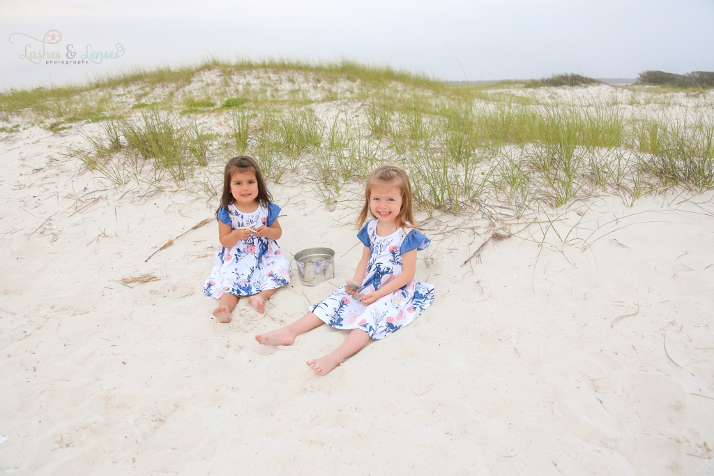 Two young sisters sitting in the sand and playing with seashells at Johnsons Beach in Perdido Key Florida