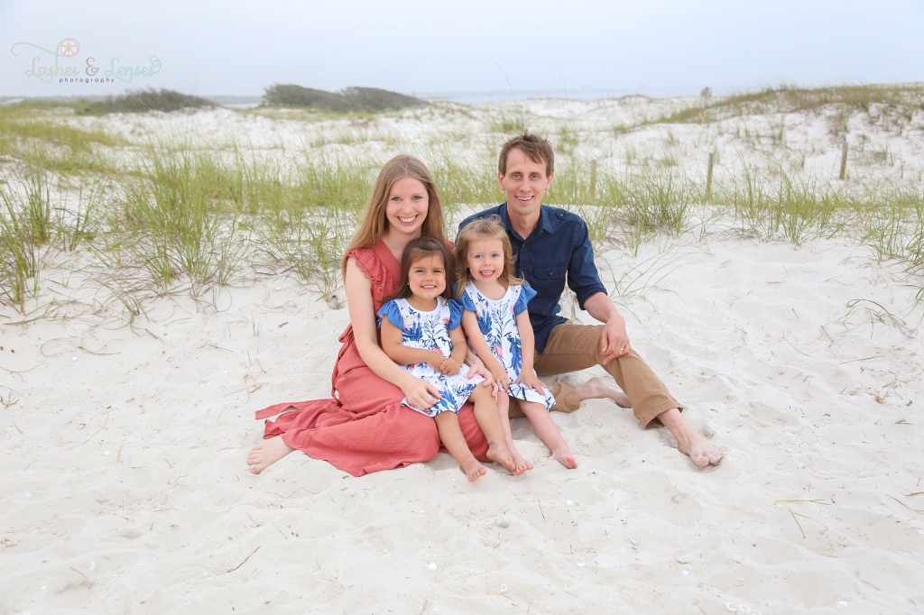 Parents sitting next to the sand dunes with their toddler daughters at Johnsons Beach in Perdido Key Florida