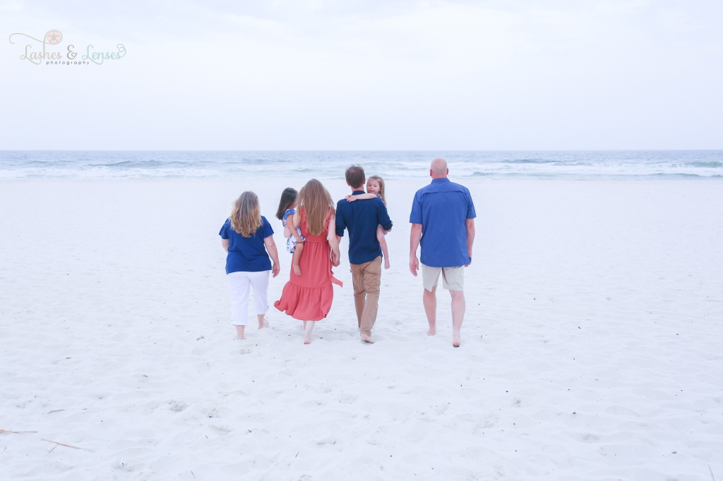 Extended family including grandparents, parents and toddler girls walking on the sand toward the water at Johnsons Beach in Perdido Key Florida