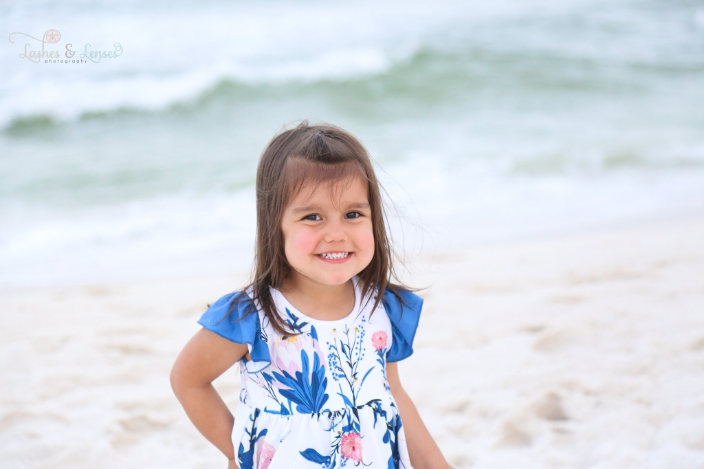 Brunette toddler girl standing with the gulf behind her at Johnsons Beach in Perdido Key Florida