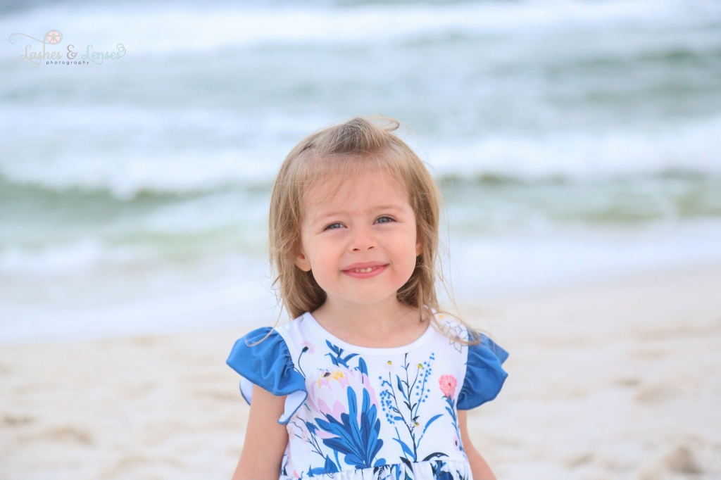 Blonde toddler girl standing with the gulf behind her at Johnsons Beach in Perdido Key Florida