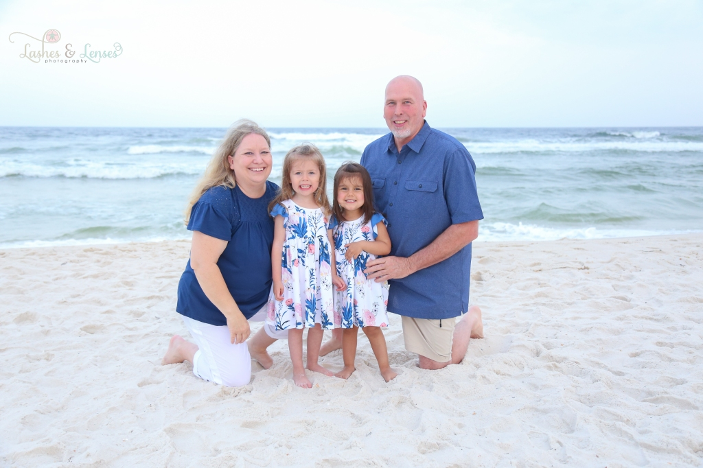 Grandparents with two young granddaughters kneeling in the sand by the water at Johnsons Beach in Perdido Key Florida