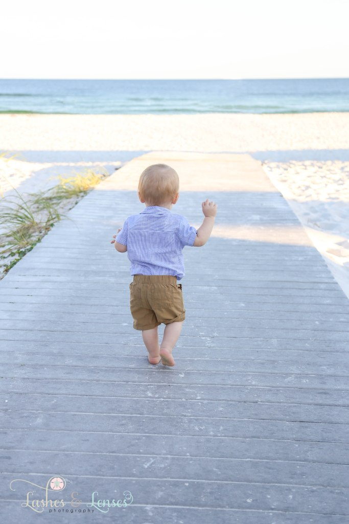 Little boy walking down boardwalk towards the beach at Johnsons Beach in Perdido Key Florida
