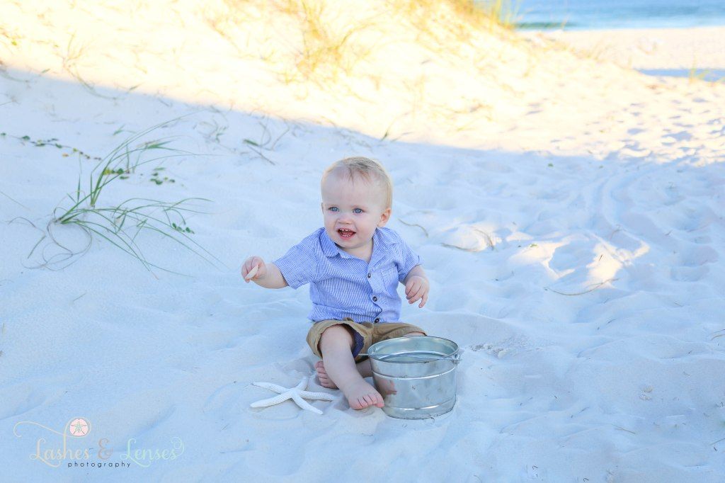 Year old little boy playing in the sand with starfish and seashell at Johnsons Beach in Perdido Key Florida