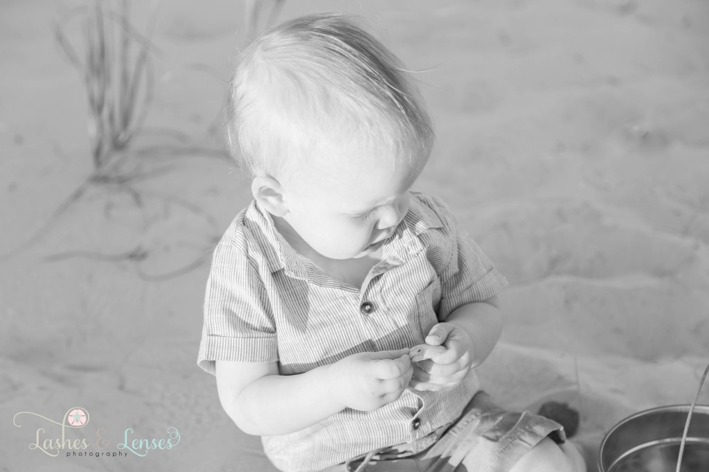 Black and White photo of little boy playing with a seashell at Johnsons Beach in Perdido Key Florida