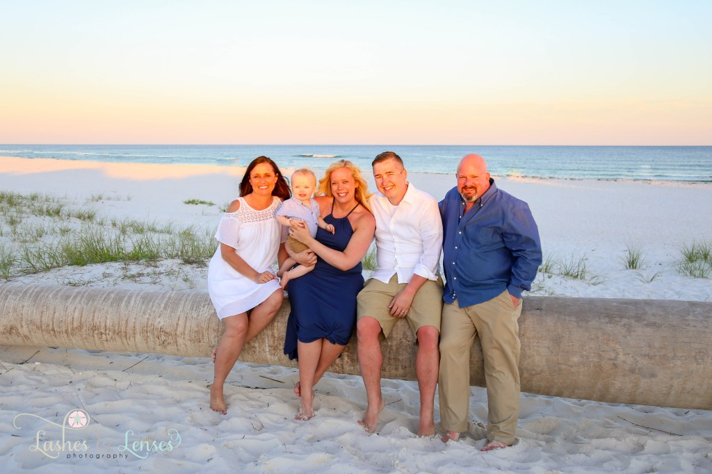 Grandparents with son and his wife and grandson sitting on a washed up palm tree at Johnsons Beach in Perdido Key Florida