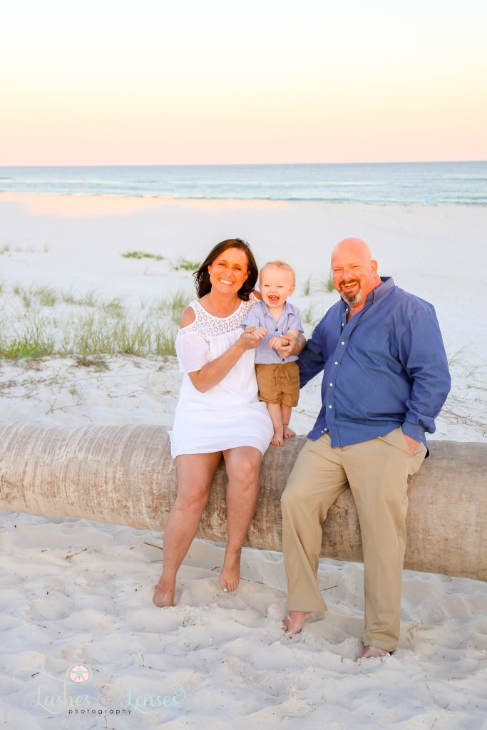 Grandparents sitting on a washed up palm tree with young grandson at Johnsons Beach in Perdido Key Florida