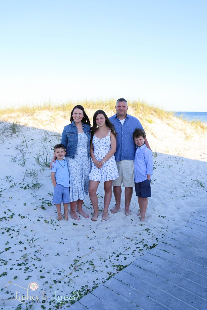 Mom and dad with their three children standing next to the sand dunes on the boardwalk at Johnsons Beach in Perdido Key Florida