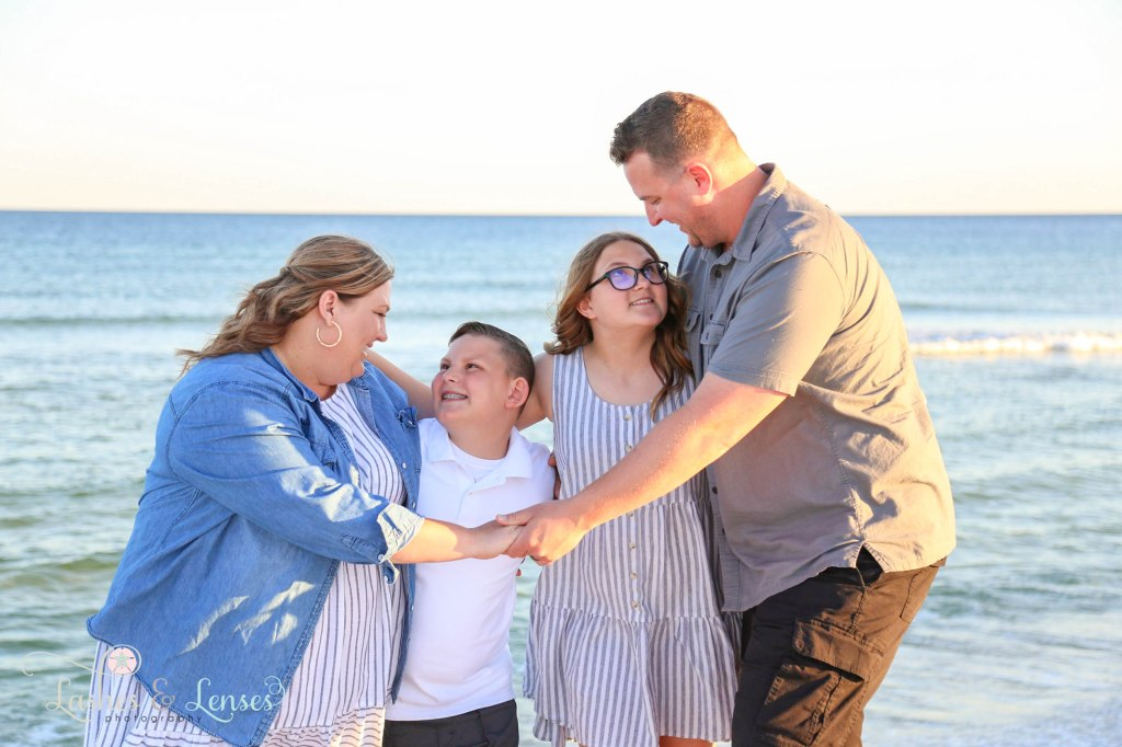 Mom and Dad hugging their teen daughter and preteen son with the gulf behind them at Johnsons Beach in Perdido Key Florida