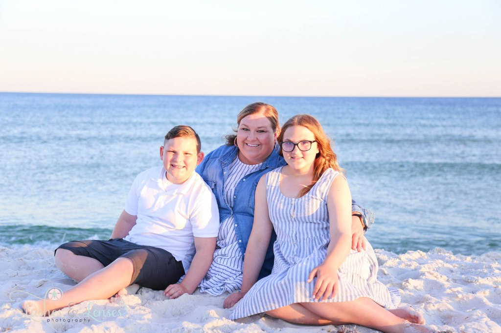 Mom with her two children sitting in the sand with the water behind them at Johnsons Beach in Perdido Key Florida