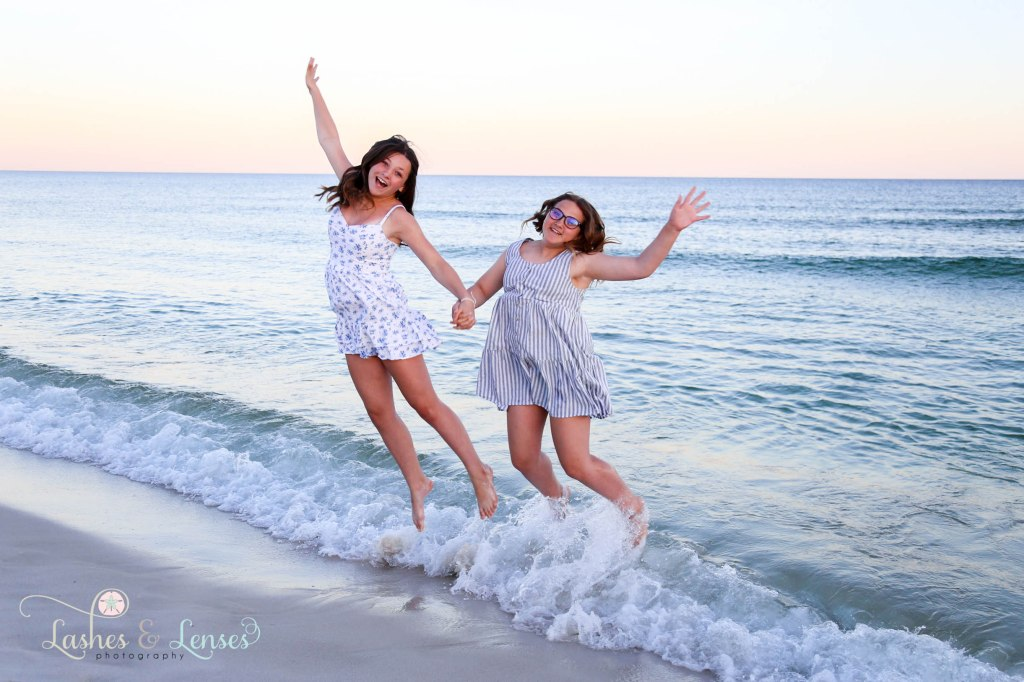Two teen girls jumping and playing in the water at Johnsons Beach in Perdido Key Florida