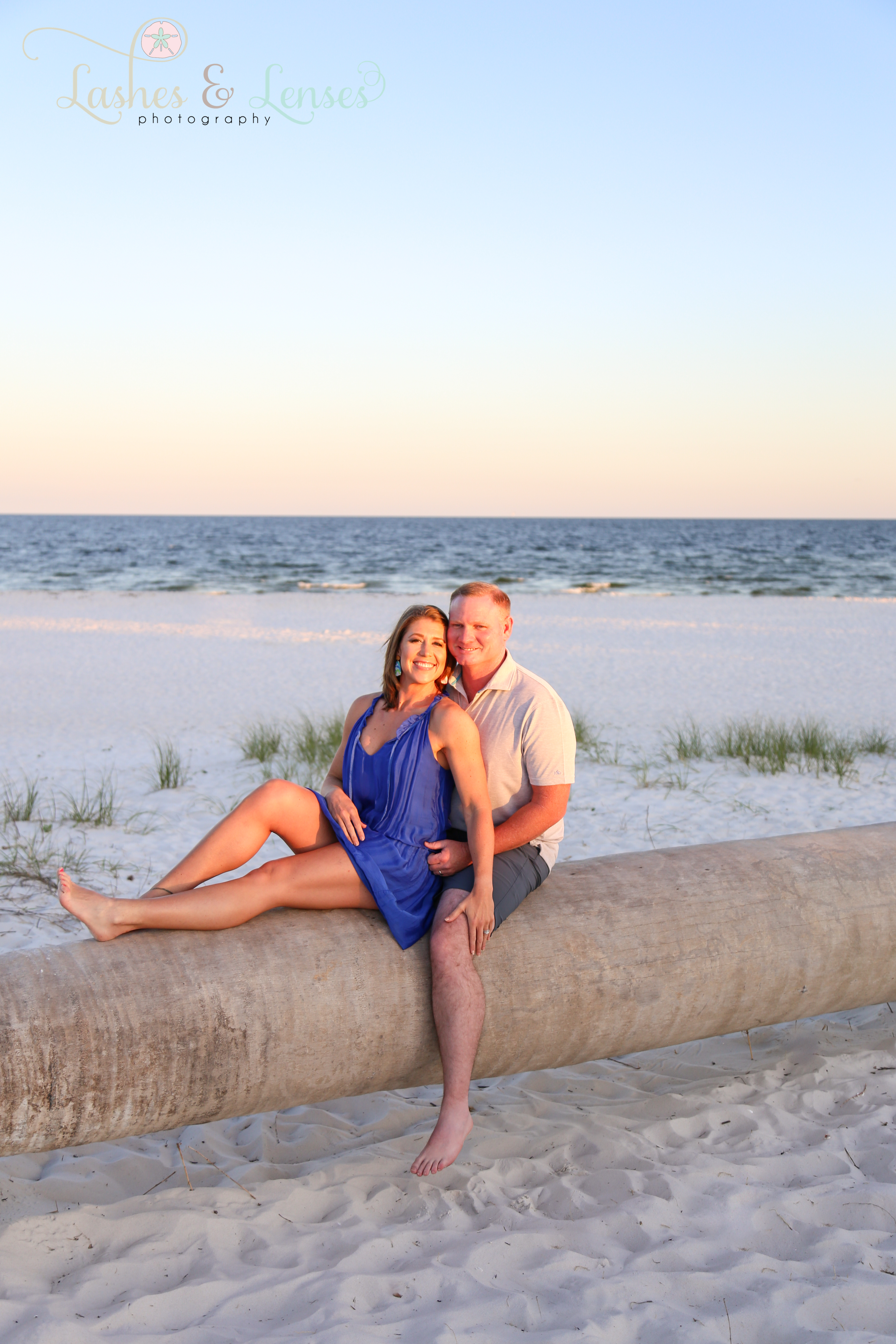 Married Couple sitting on a washed up palm tree with the gulf behind them  at Johnsons Beach in Perdido Key Florida