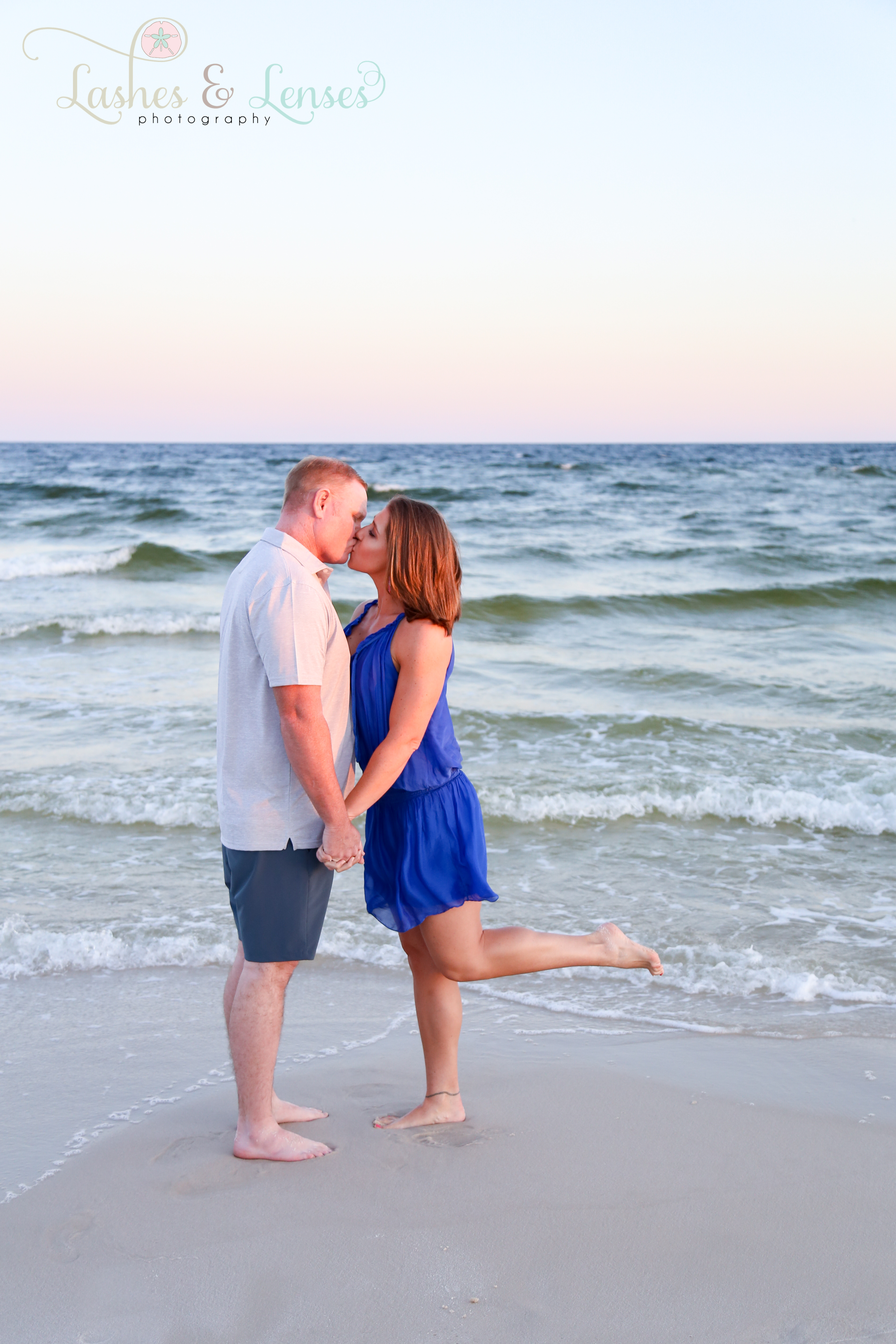Husband and Wife kissing next to the water.  at Johnsons Beach in Perdido Key Florida