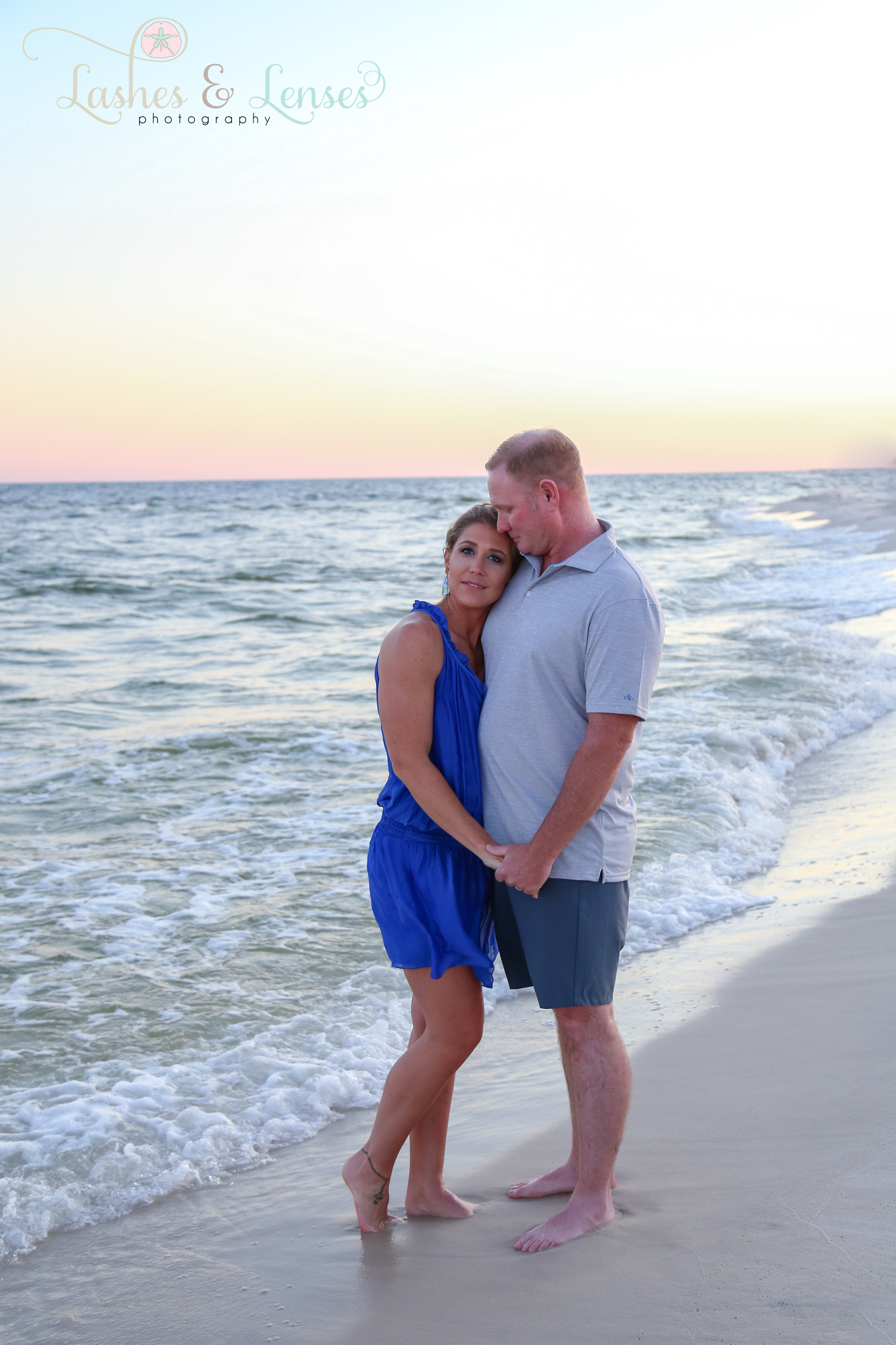 Husband kissing wife's temple next to the water  at Johnsons Beach in Perdido Key Florida