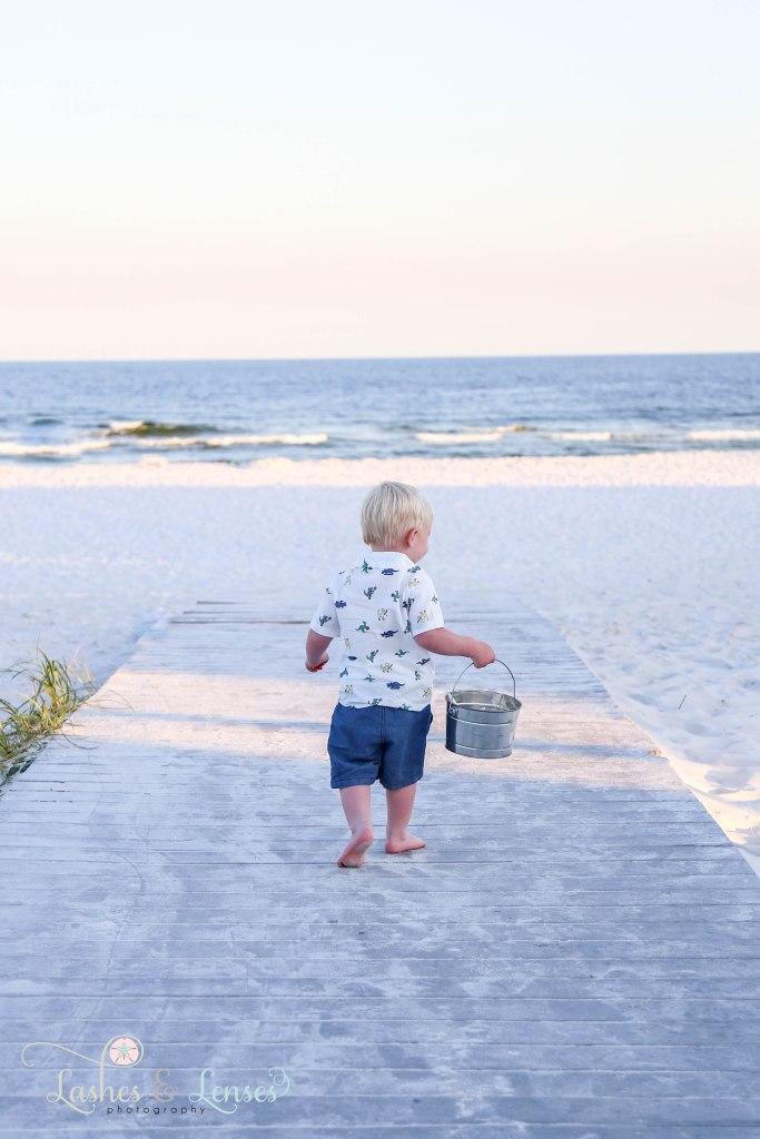 Toddler boy walking down the boardwalk towards the beach at Johnsons Beach in Perdido Key Florida