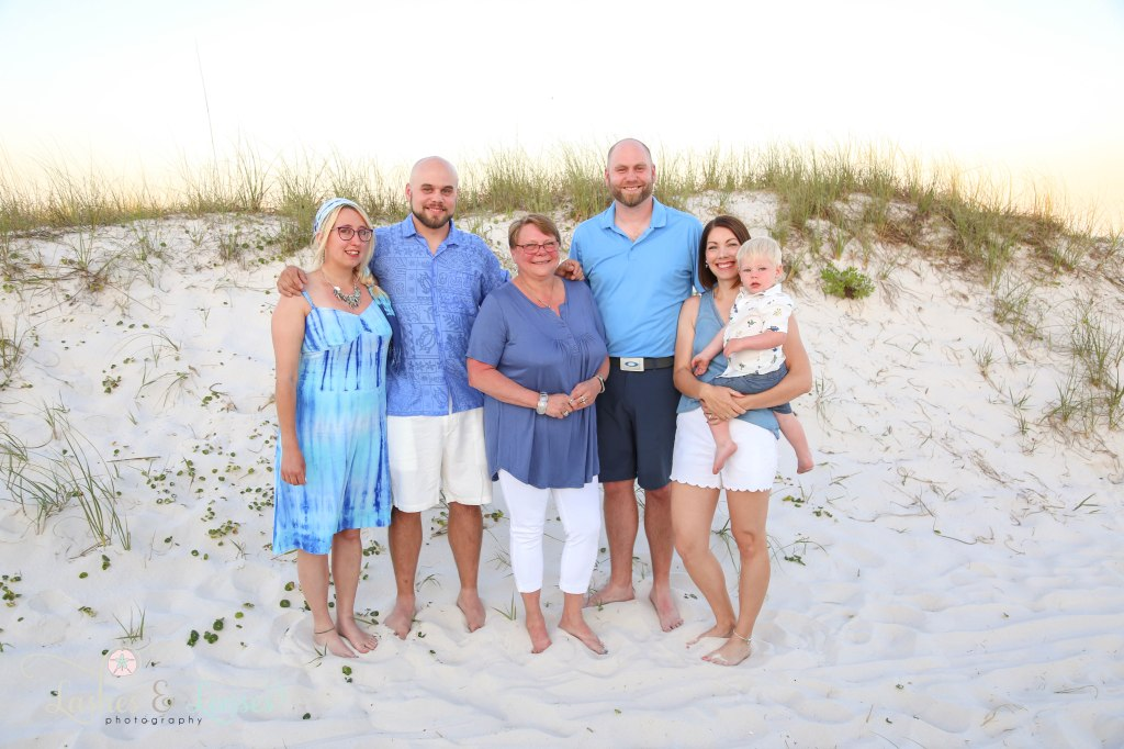 Extended family standing next to the sand dunes at Johnsons Beach in Perdido Key Florida