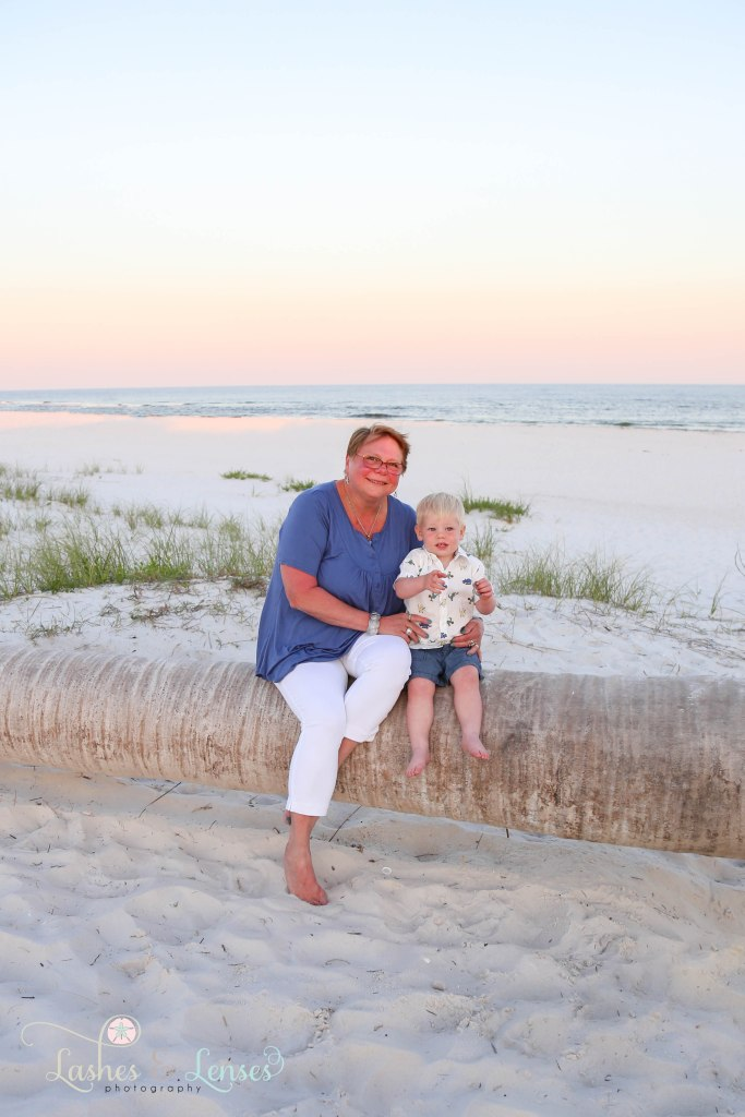 Grandma and grandson sitting on a washed up palm tree with the water behind them at Johnsons Beach in Perdido Key Florida