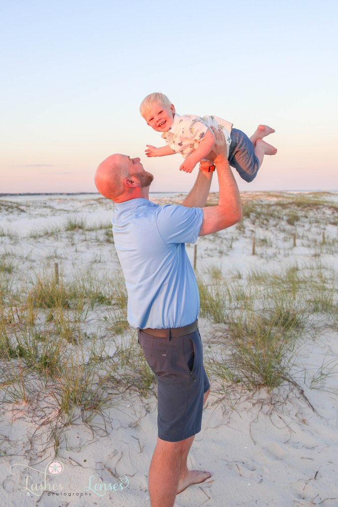 Dad swinging son in the air with the sand dunes behind them at Johnsons Beach in Perdido Key Florida