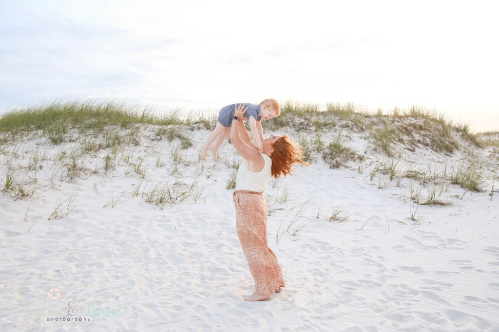 Mom holding young son above her head playing in the sand dunes at Johnsons Beach in Perdido Key Florida