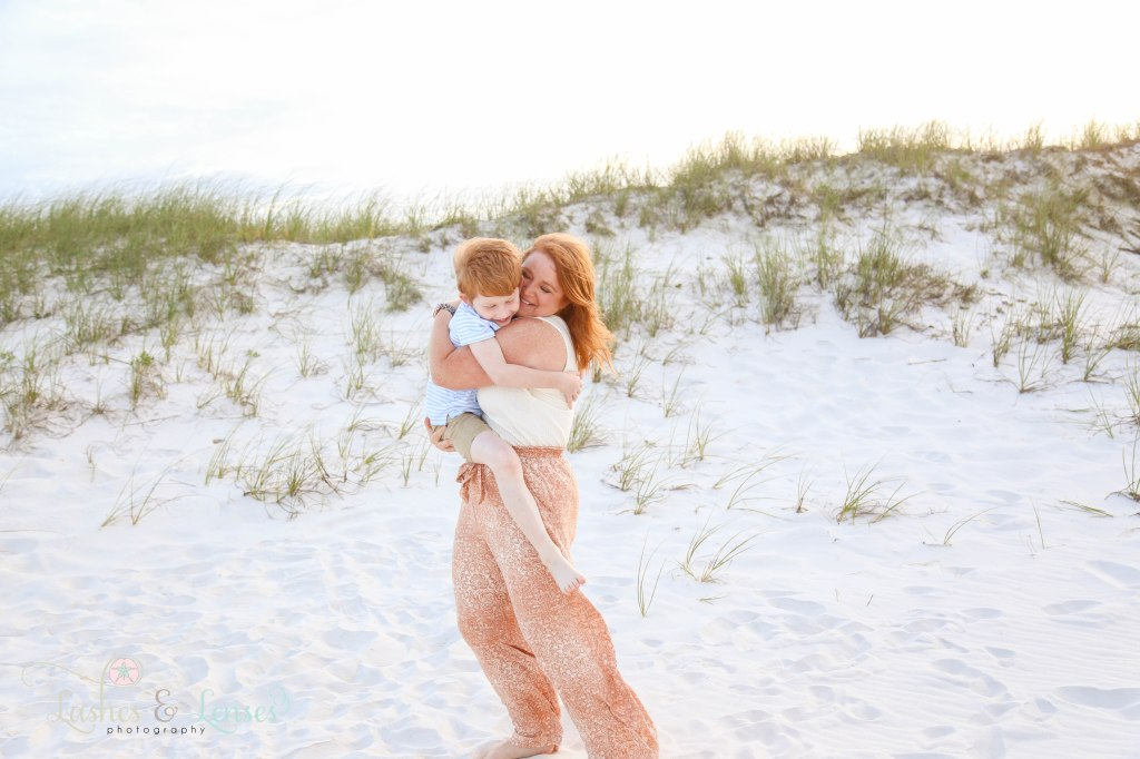 Mom hugging son and spinning him around next to the sand dunes at Johnsons Beach in Perdido Key Florida