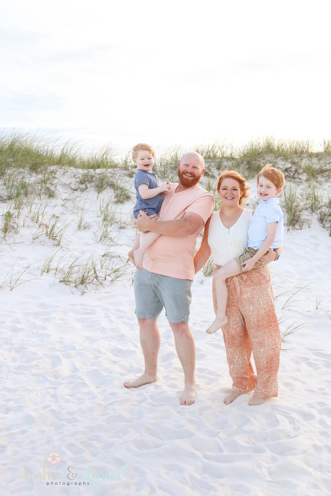 Mom and dad both holding their sons standing next to the sand dunes at Johnsons Beach in Perdido Key Florida