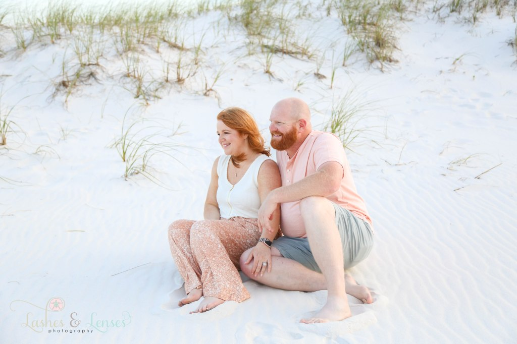 Parents smiling at their young sons and looking away from the camera sitting in the sand at Johnsons Beach in Perdido Key Florida