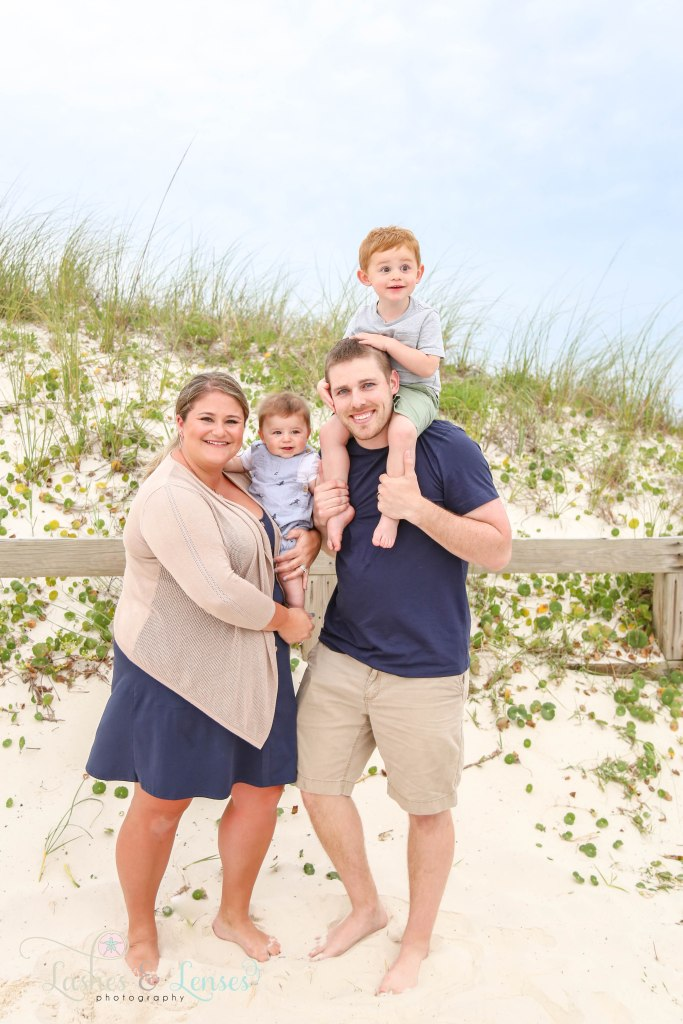 Mom holding baby son on hip and dad with 2 year old son on his shoulders standing next to a sand dune at Johnsons Beach in Perdido Key Florida