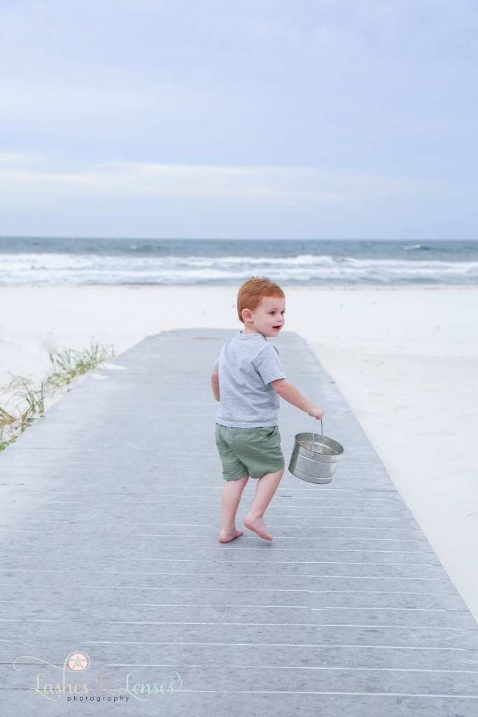Two year old boy walking down the boardwalk with a bucket in his hands at Johnsons Beach in Perdido Key Florida