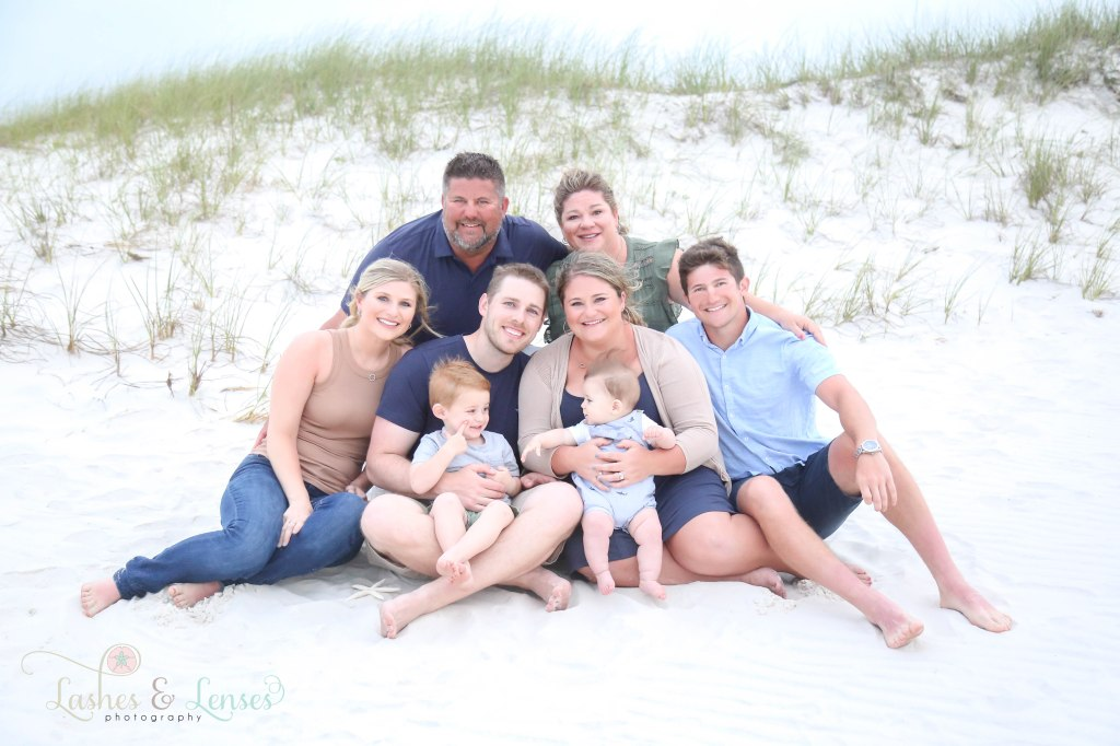 Extended family sitting in the sand and the two young brothers looking at each other at Johnsons Beach in Perdido Key Florida