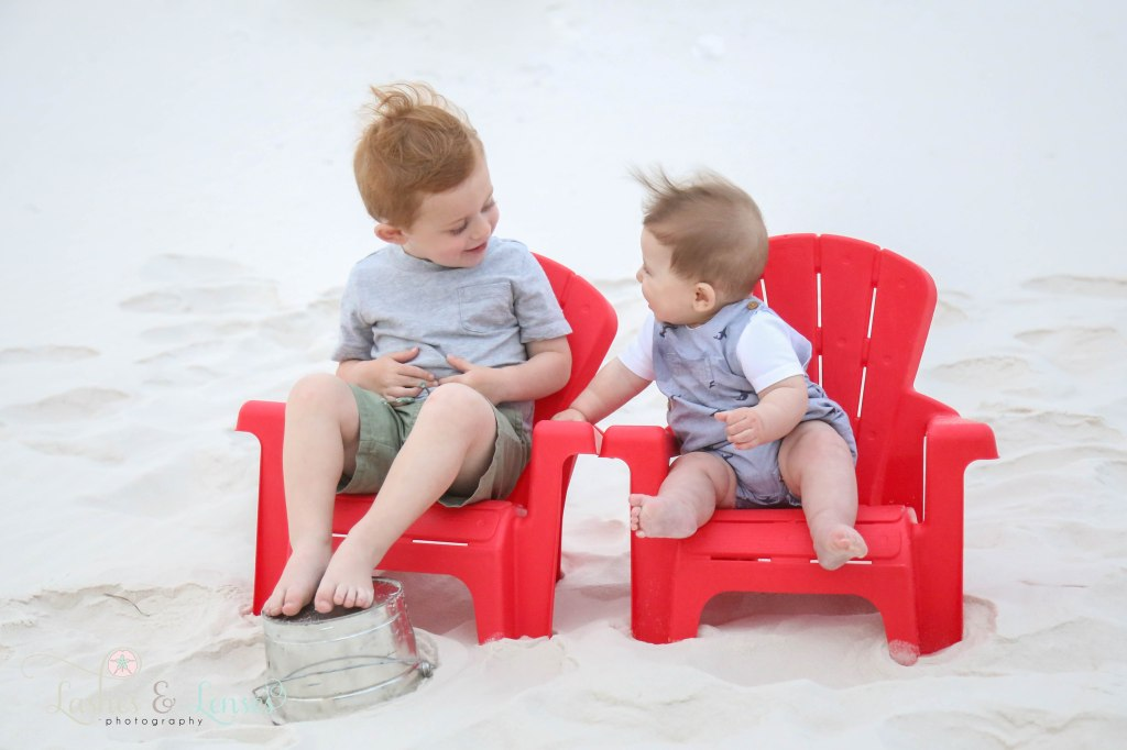 Brothers sitting and talking in their Adirondack chairs in the sand at Johnsons Beach in Perdido Key Florida