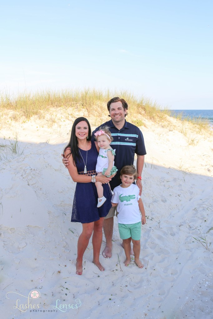 Mom and Dad with their young son and daughter standing next to the sand dunes at Johnsons Beach in Perdido Key