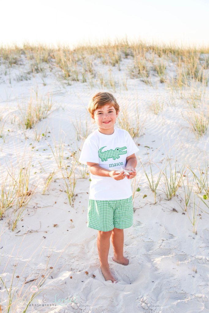 Toddler boy holding a starfish in his hands in the sand dunes at Johnsons Beach in Perdido Key