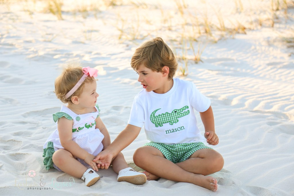 Brother holding his baby sister's hand while sitting in the sand at Johnsons Beach in Perdido Key