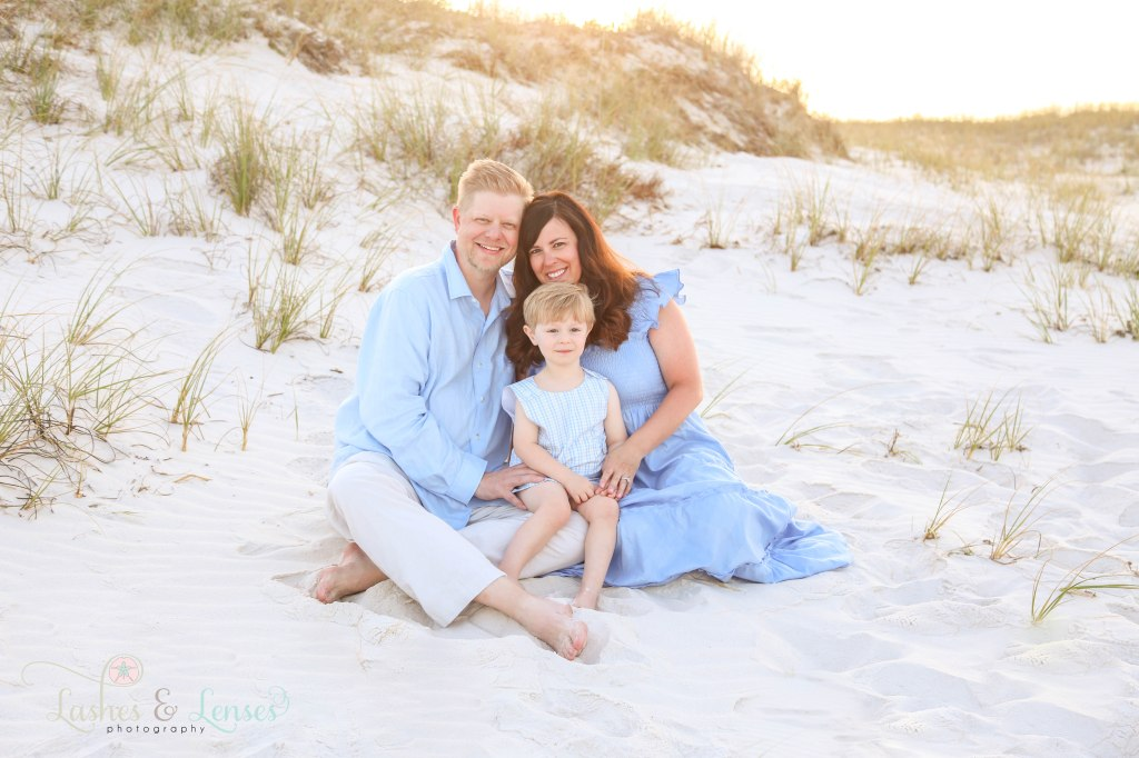 Mom and Dad sitting next to the sand dunes with their toddler son at Johnsons Beach in Perdido Key Florida