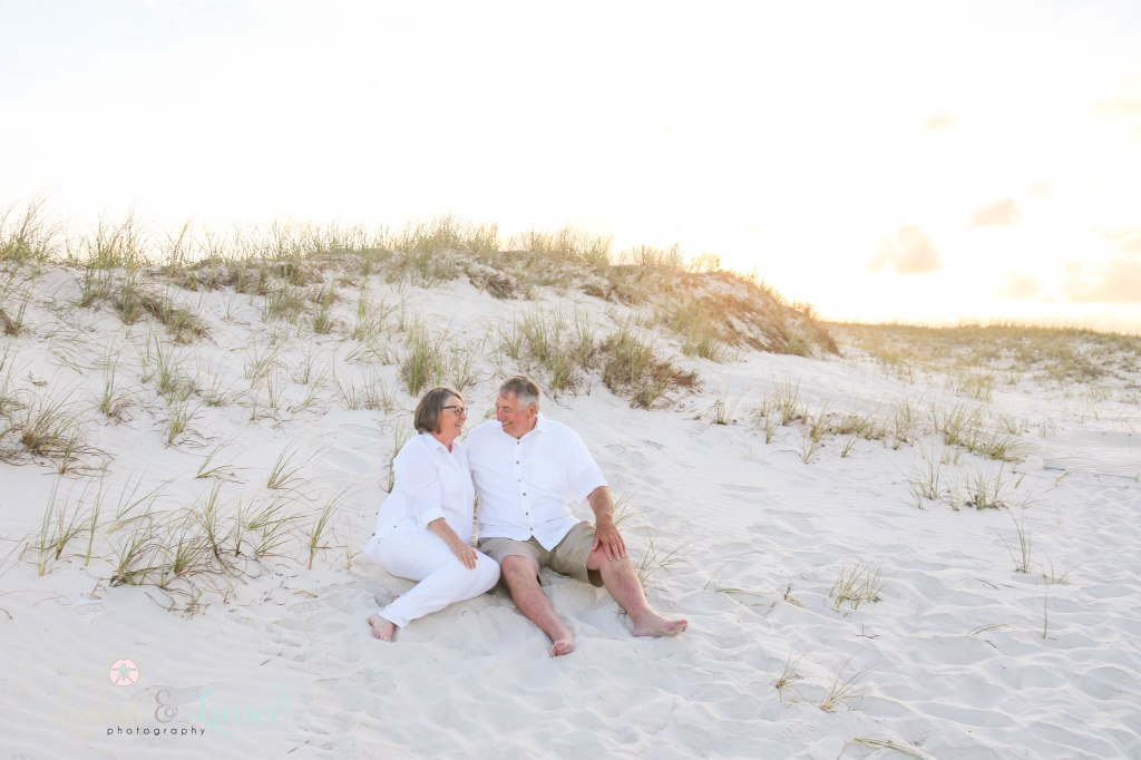 Grandparents celebrating their 50th anniversary and sitting in the sand at Johnsons Beach in Perdido Key Florida