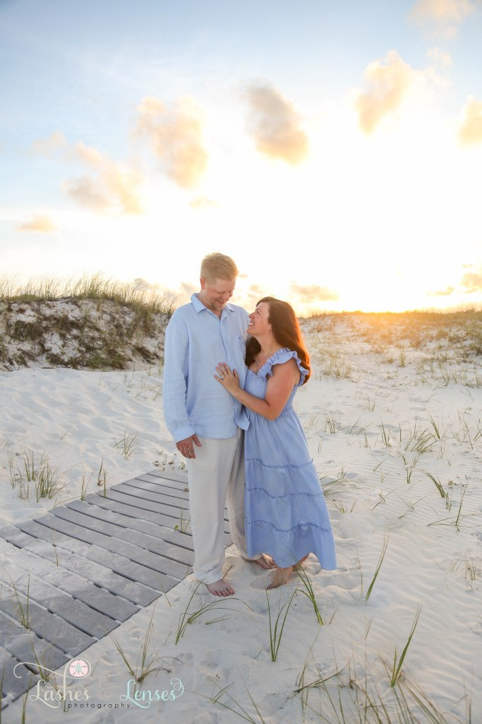 Husband and wife standing in the sand with the sunset behind them at Johnsons Beach in Perdido Key Florida