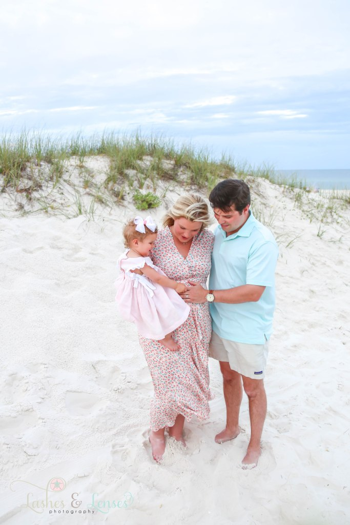 Baby and Dad holding pregnant moms belly in the sand at Johnsons Beach in Perdido Key Florida