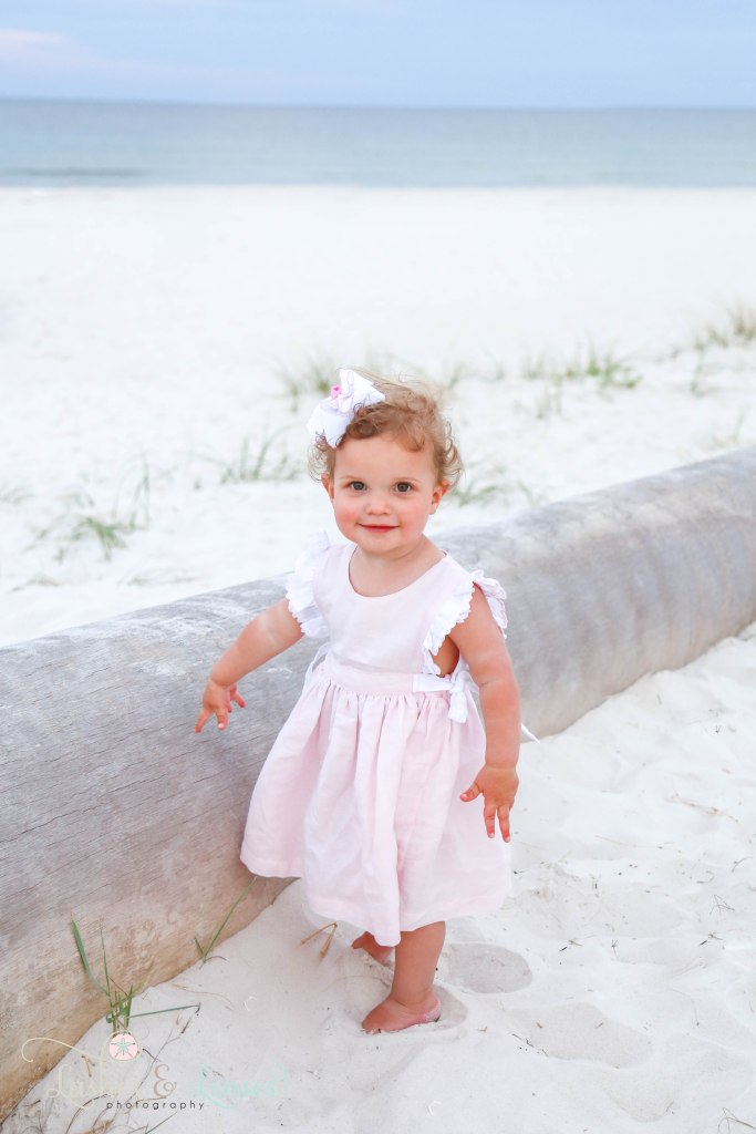 Toddler girl in pink ruffle dress standing next to a washed up palm tree at Johnsons Beach in Perdido Key Florida