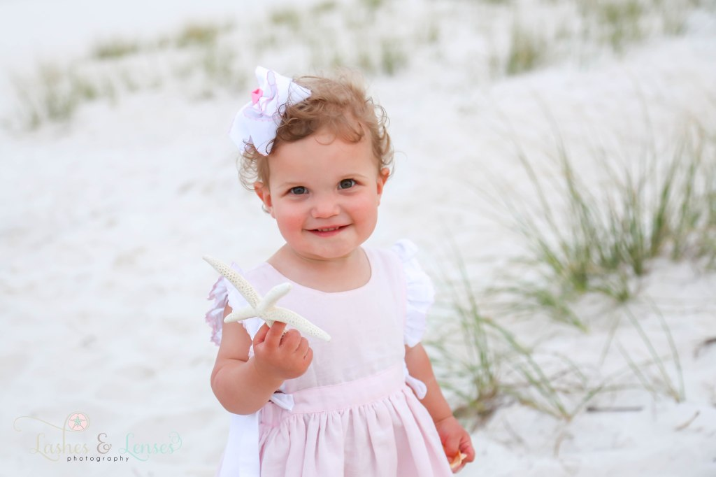 Toddler girl in pink ruffle dress holding a starfish next to the sand dunes at Johnsons Beach in Perdido Key Florida