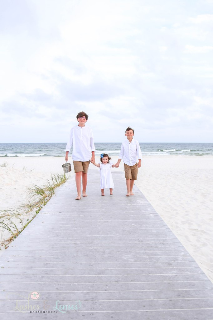 Brothers and Sister walking on the boardwalk with the water behind them at Johnsons Beach in Perdido Key Florida