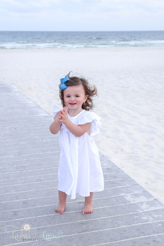 Toddler girl clapping her hands and standing on the boardwalk with the gulf behind her at Johnsons Beach in Perdido Key Florida